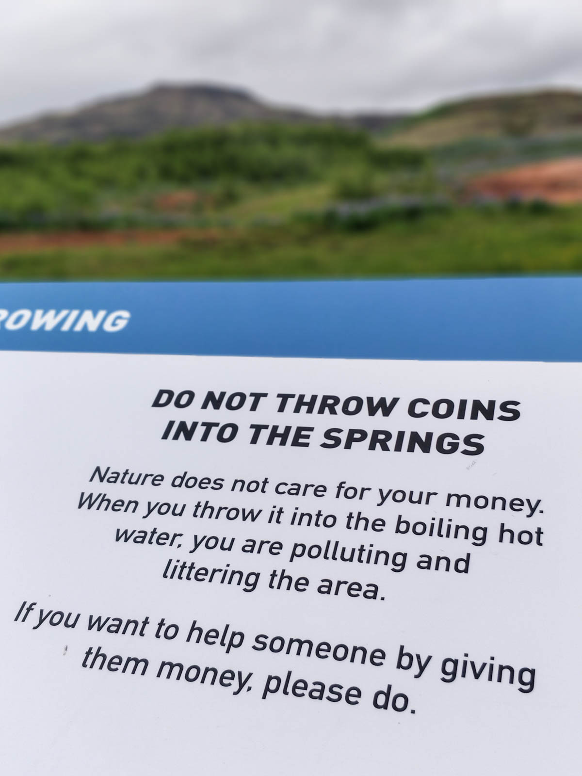 Schild: Do not throw coins into the springs. Nature does not care for your money. When you throw it into the boiling hot water, you are polluting and littering the area. If you want to help someone by giving them money, please do.